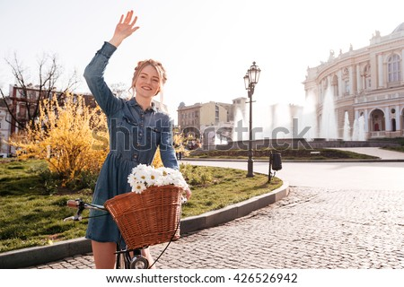 Cheerful lovely young woman with bike standing and waving her hand on the street - stock photo