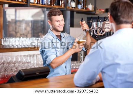 Cheerful male barman is serving his customer. He is pouring beer in glass and smiling. The man is sitting at counter and waiting for his order