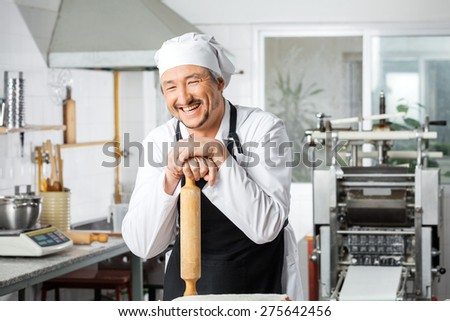 Cheerful male chef leaning on rolling pin in commercial kitchen - stock photo