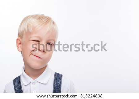 Cheerful male child is standing and grimacing. He is looking forward and winking. The schoolboy is smiling. Isolated and copy space in right side - stock photo
