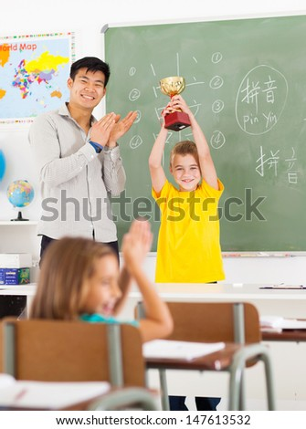cheerful male chinese language teacher applauding for student who won a trophy