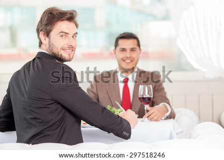 Cheerful male colleagues are sitting at the table in cafe. They are eating and laughing. The men discuss a contract and looking at the camera with joy. Copy space in right side - stock photo