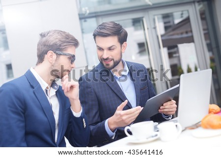 Cheerful male colleagues have discussion in restaurant - stock photo