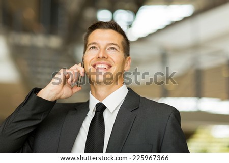 cheerful male corporate worker talking on cell phone - stock photo