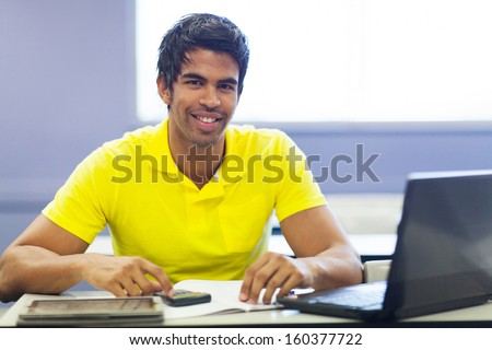 cheerful male indian college student in lecture room - stock photo