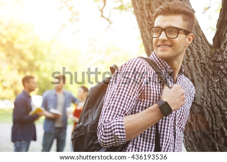 Cheerful male student is relaxing in the nature - stock photo