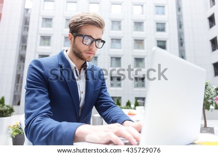 Cheerful male working is using laptop in cafe - stock photo