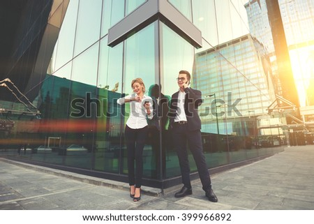 Cheerful man boss is having pleasant mobile phone conversation with client,while his female secretary with smile is checking time before their meeting with partners and holding cell telephone in hand  - stock photo