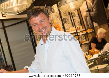 Cheerful man buying some cakes in a pastry shop