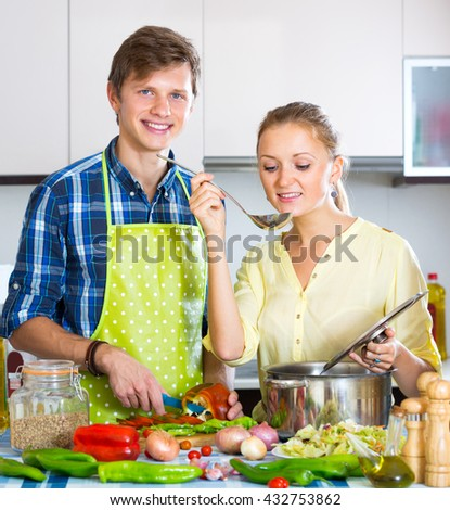 Cheerful man helping young wife to prepare healthy dinner - stock photo