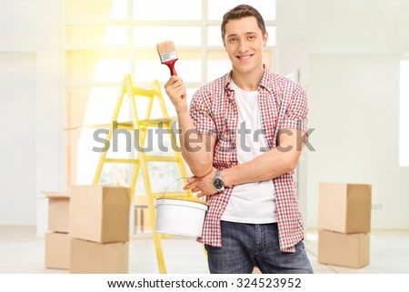 Cheerful man holding a paintbrush and a color bucket in a new apartment with a few cardboard boxes and a yellow ladder behind him - stock photo