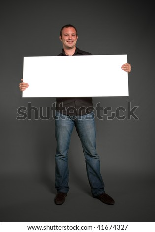 Cheerful man holding blank message board - stock photo