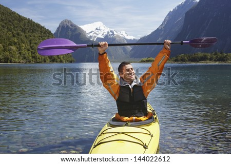 Cheerful man holding up kayak oar over head in mountain lake - stock photo