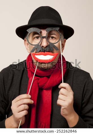 Cheerful man in a carnival mask and a black hat - stock photo