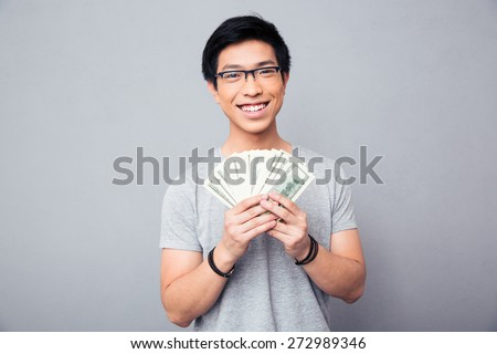 Cheerful man in glasses holding bills of US dollars over gray background and looking at camera - stock photo