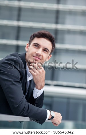 Cheerful man in suit is waiting for his business partner outdoors. He is leaning on the border and touching his chin pensively. The man is looking aside with anticipation - stock photo