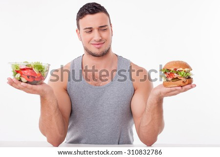 Cheerful man is holding a bowl of salad and a hamburger in his hands. The man is looking at unhealthy food with disgust. The boy is sitting at the table. Isolated on background - stock photo