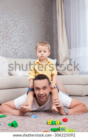 Cheerful man is playing with his son. He is lying on flooring and holding a kid on his shoulders. The man is looking at the camera and smiling. A boy is sitting with joy - stock photo