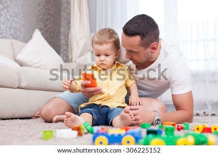 Cheerful man is sitting near his son on flooring. He is showing him a mobile phone with joy. The little boy is looking at the telephone with interest - stock photo