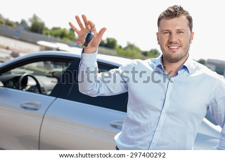 Cheerful man is standing near his car and holding its key in his hand. He is smiling boastfully and looking at the camera - stock photo