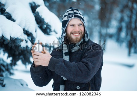 Cheerful man playing in the snow - stock photo