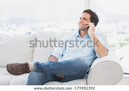 Cheerful man sitting on the couch making a phone call at home in the living room - stock photo