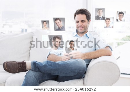 Cheerful man sitting on the couch using his smartphone against profile pictures - stock photo