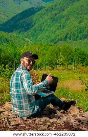 Cheerful man smiling no camera and showing thumbs up outdoors in the mountains - stock photo