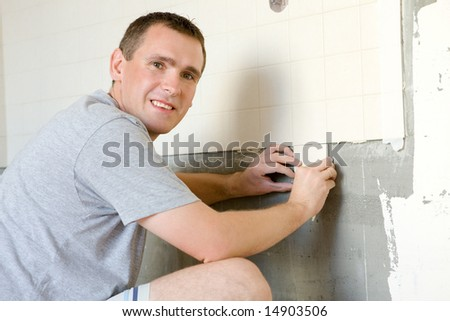Cheerful man tiling a wall