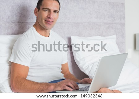 Cheerful man using laptop on bed smiling at camera at home in the bedroom - stock photo