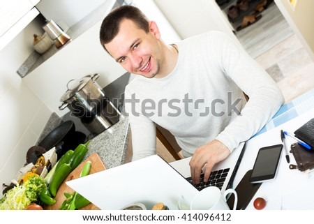 Cheerful man with laptop at table in home interior