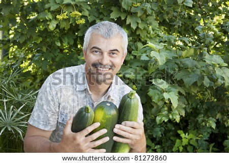 Cheerful man with three zucchini in garden