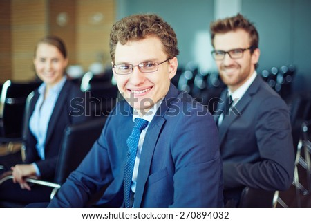 Cheerful manager looking at camera with two colleagues behind - stock photo
