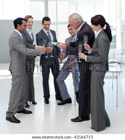 Cheerful manager serving Champagne to his team to celebrate a success - stock photo