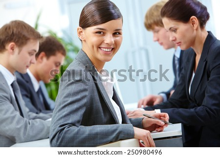 Cheerful manager sitting at workplace on background of working partners