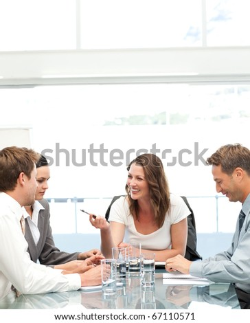 Cheerful manager talking to her team during a meeting in the office - stock photo