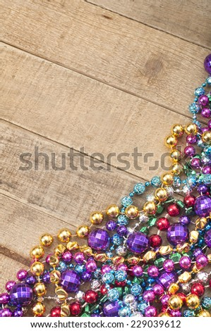 Cheerful Mardi Gras Beads in corner on Rustic Wood Board Background with room or space for copy, text, your words.  Vertical from above. - stock photo