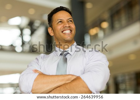 cheerful mature businessman looking up in office - stock photo