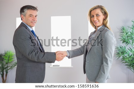 Cheerful mature businessman shaking the hand on a content blonde businesswoman both looking at camera at office - stock photo