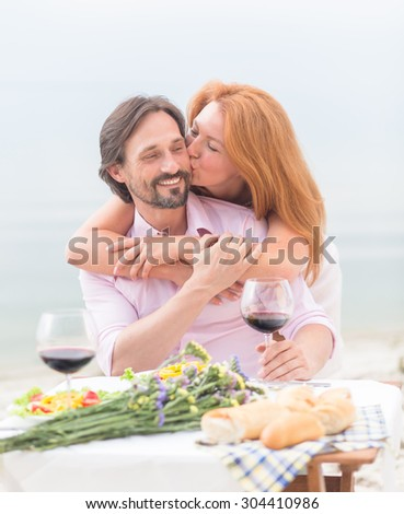 Cheerful mature couple embracing by the beach. Red-haired woman kissing her husband isolated on sea.