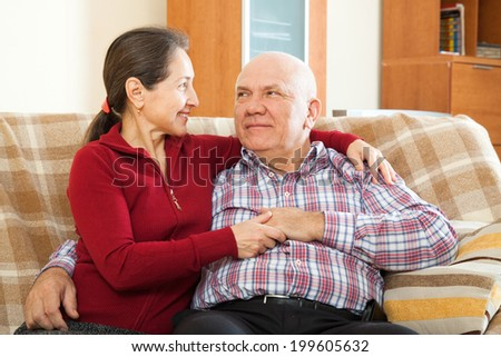 cheerful  mature couple on sofa in home