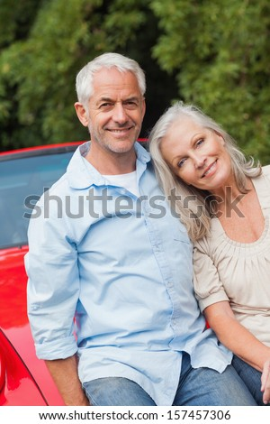 Cheerful mature couple sitting on their red convertible on bright day - stock photo