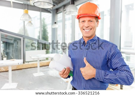 Cheerful mature engineer is satisfied with his work. He is giving thumb up and smiling. The man is standing and holding a blueprint. Copy space in left side - stock photo