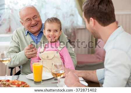 Cheerful mature grandfather is dining with his children - stock photo