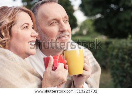Cheerful mature husband and wife are drinking tea outdoors. They are sitting and embracing. The man and woman are warming with quilt. They are smiling - stock photo