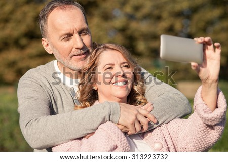 Cheerful mature loving couple is photographing themselves. They are standing and smiling. The man is embracing the woman with love. The lady is holding a mobile phone - stock photo