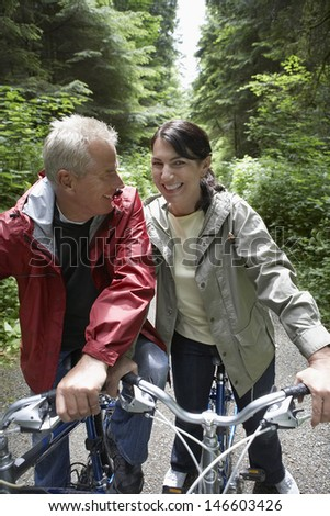 Cheerful mature man and middle aged woman with bikes in forest