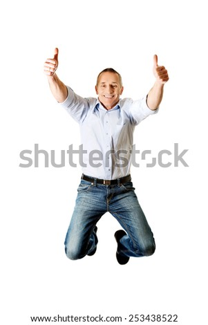Cheerful mature man jumping with thumbs up. - stock photo