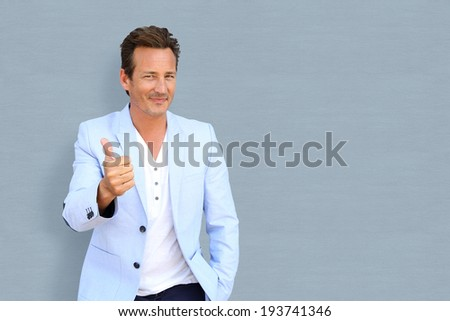 Cheerful mature man showing thumbs up - stock photo
