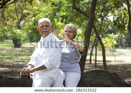 Cheerful mature woman and man having fun while sitting on tree trunk in park - stock photo